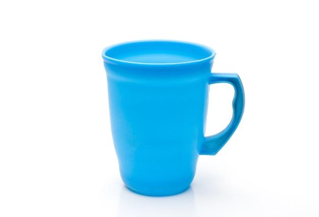 青い色のプラスチックガラスまたは水差しは、反射と孤立した白い背景にクローズアップ