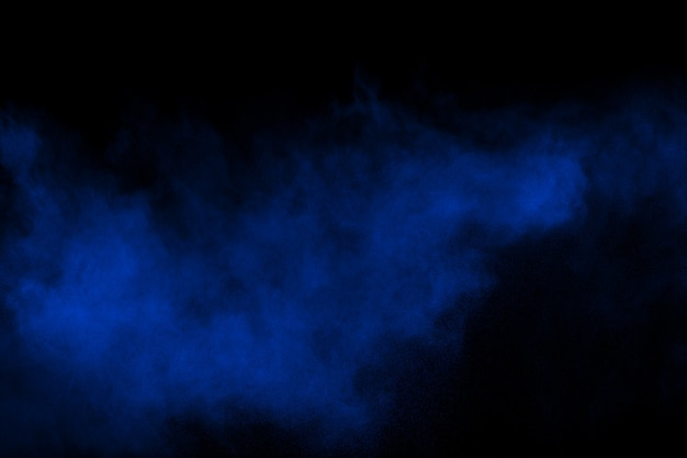 Blue color powder explosion cloud. closeup of blue dust particles exhale on dark background.