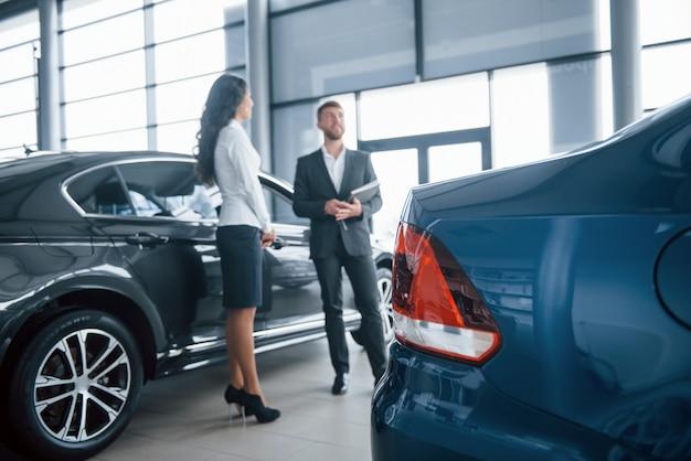 青い色の車。女性客と自動車サロンでモダンなスタイリッシュなひげを生やした実業家