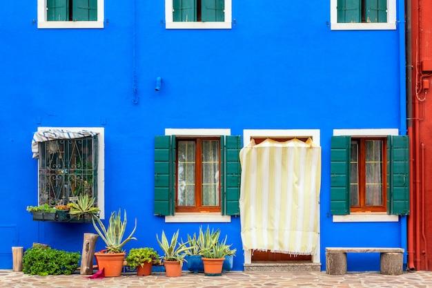 Дом синего цвета с цветами и скамейке. красочные дома в остров бурано возле венеции, италия.