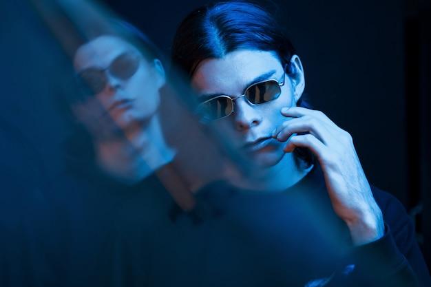 파란색 조명. 쌍둥이 형제의 초상화입니다. 네온이있는 어두운 스튜디오에서 촬영 한 스튜디오