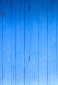 Blue colored painted rough wooden fence, floor or wall panel board background