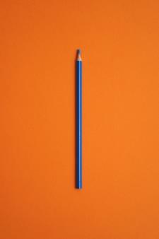 Синий цветной карандаш на оранжевом фоне