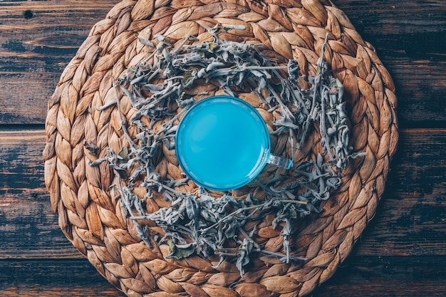 Blue colored water in a trivet with tea top view on a dark wooden background