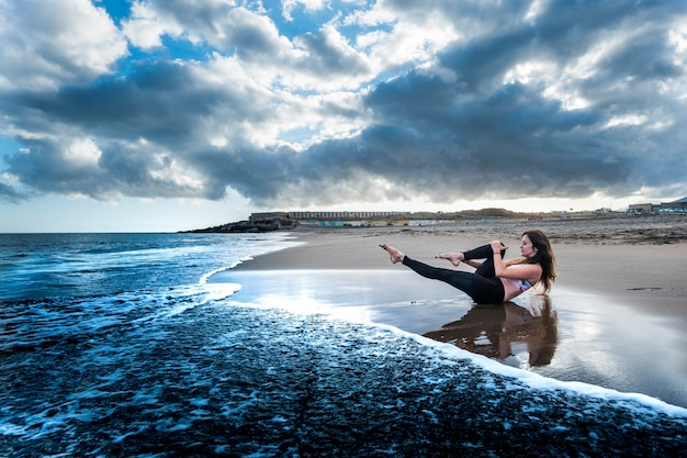 Blue colors epic style image with pretty brunette doing sport and pilates activity at the beach on the shore
