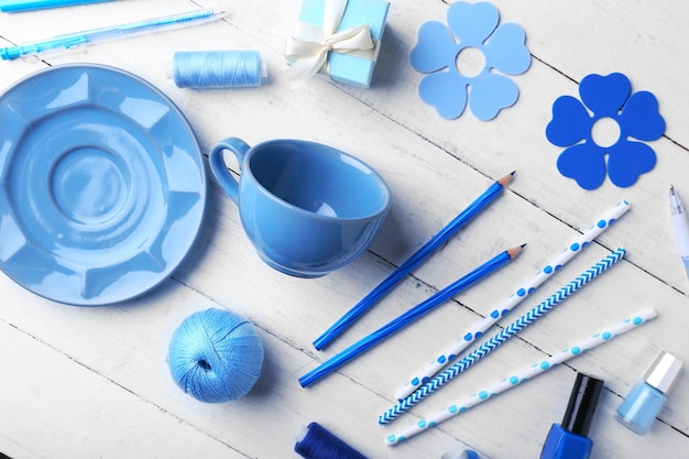 Blue colour flat lay composition on white wooden table