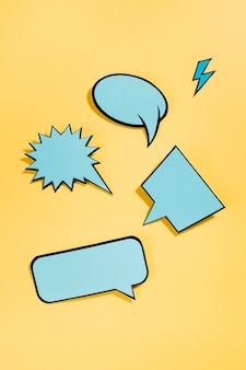 Blue comic speech bubbles with black border on yellow backdrop
