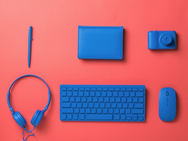 Blue computer and office accessories on a red background. stylish accessories for business and freelancing. flat lay.