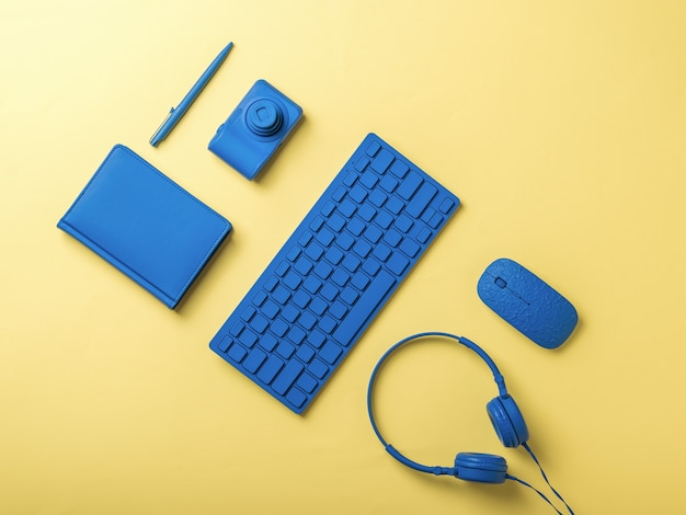 Blue computer and stationery accessories on a yellow background. stylish accessories for business and freelancing. flat lay.