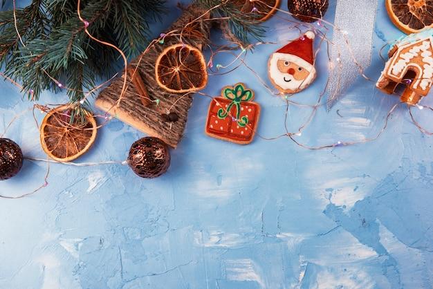 モミの枝、おもちゃの花輪と装飾が施された青いコンクリートの表面