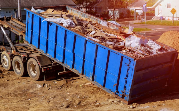 Blue construction debris container filled with rock and concrete rubble