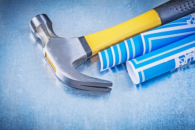 Blue construction drawings claw hammer on metallic background