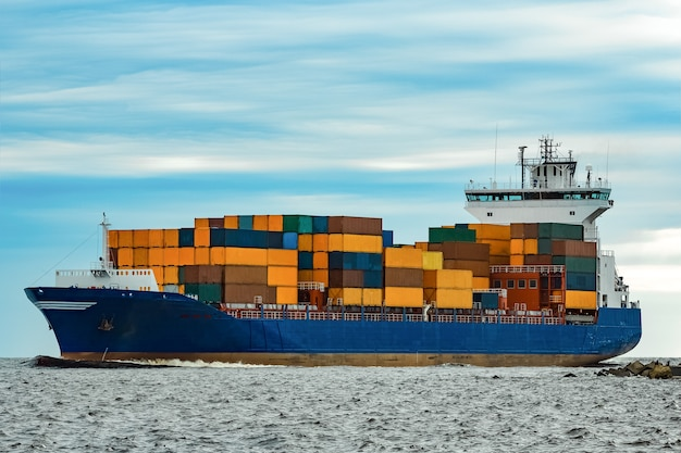 Синий контейнеровоз, полностью загруженный, движется от моря