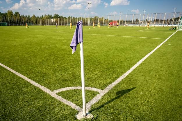 晴れた日のサッカー フィールドの青いコーナー フラグ
