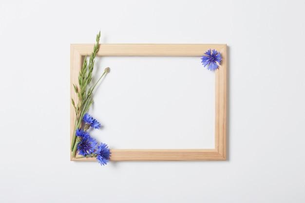 Синие васильки и деревянная рама на белой поверхности