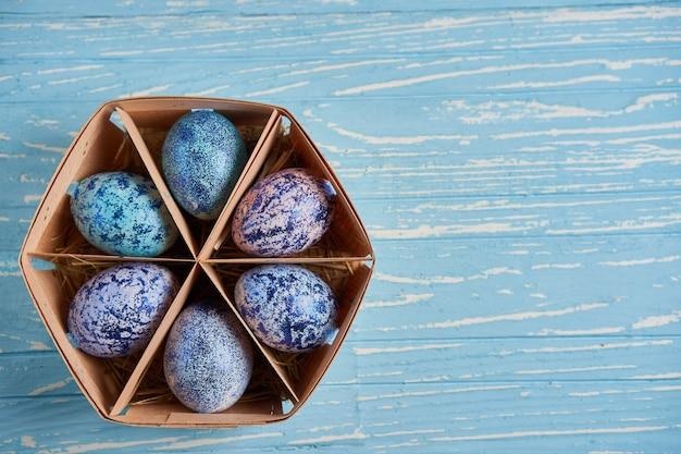 푸른 코스모스 닭고기 달걀은 푸른 나무 테이블에 서있는 둥근 나무 바구니에 놓여 있습니다.