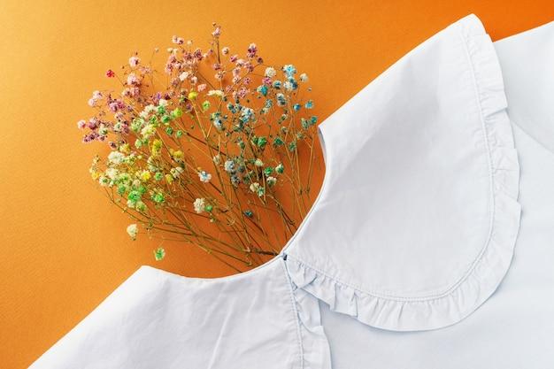 밝은 갈색 배경에 멋진 칼라와 꽃이 있는 파란색 면 티셔츠. 가을 의류 컨셉의 패션 컬렉션입니다. 창의적인 티셔츠 레이아웃 디자인. 꽃으로 사람의 머리를 모방합니다.