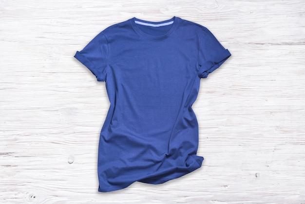 Синяя хлопковая футболка на деревянном фоне,