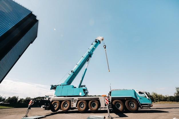Blue crane lifting mechanism with hooks near the glass modern building,