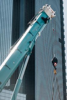 ガラスの近代的な建物の近くにフックが付いたハゴロモヅルの吊り上げ機構、クレーン、最大120メートルの油圧式高揚力