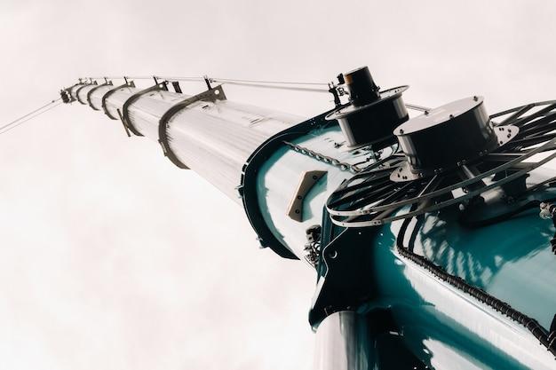 Подъемный механизм синего крана с крюками возле стеклянного современного здания,