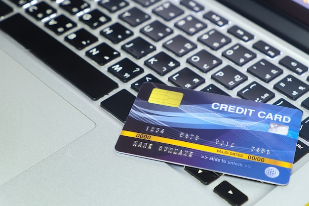 Blue credit card on locked mode put on keyboard of modern laptop online shopping and payment via credit card
