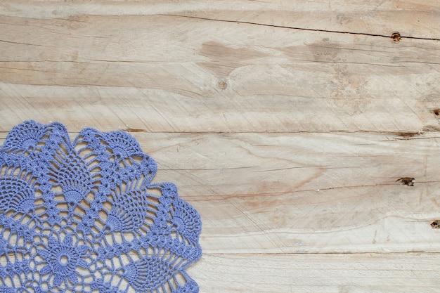 古い木製のテーブルの上の青いかぎ針編みのドイリー