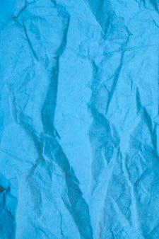 Blue crumpled paper background.