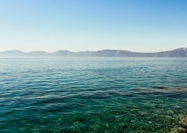 Голубое кристаллическое идиллическое озеро с горной цепью против голубого неба