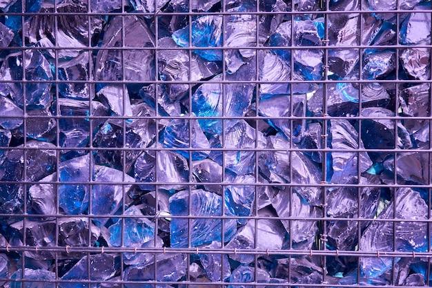 ブルークリスタルミネラルストーン。宝石。石の檻の人工結晶現代建築壁の背景貴石と半貴石の質感。貴石の着色された光沢のある表面