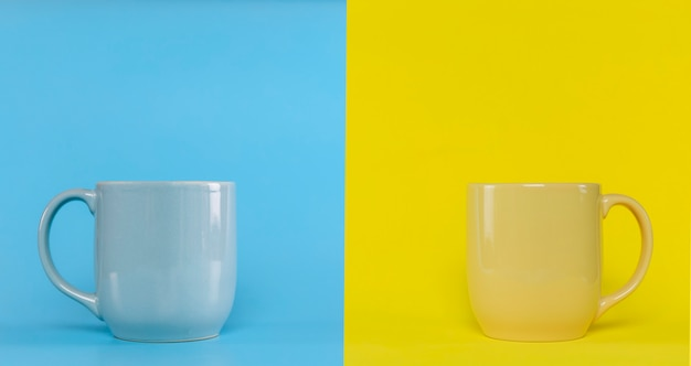 Blue cup on blue background and yellow cup on yellow background with copy space. blue cup with handle and yellow with handle.