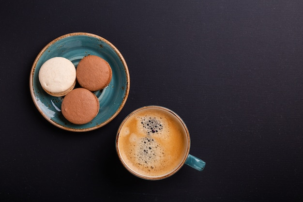 Blue cup of coffee and macaroons on the dark wooden table