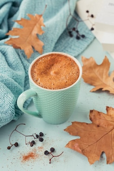 Blue cup of coffee with autumnal dry leaves and dry berries on light blue