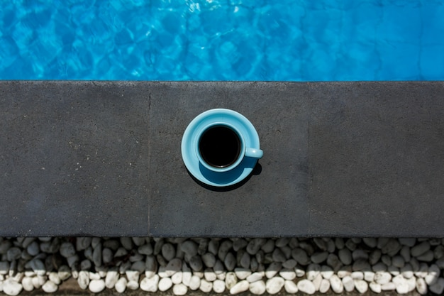 Blue cup of hot coffee next to poolside