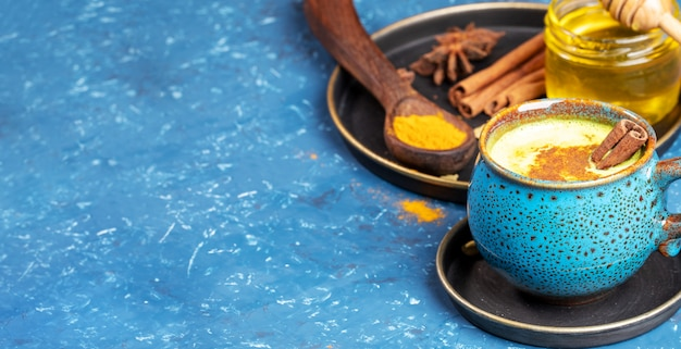 Blue cup of indian ayurvedic healthy drink - golden turmeric latte milk and plate with ingredients on blue. copy space.