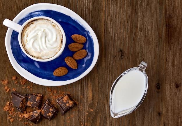 Синяя чашка капучино, миндаль, шоколад и молоко в стеклянном кувшине для молока