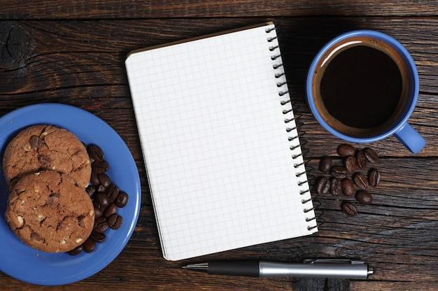 파란색 커피, 쿠키, 나무 탁자 위에 열린 메모장, 위쪽 전망. 텍스트를 위한 공간