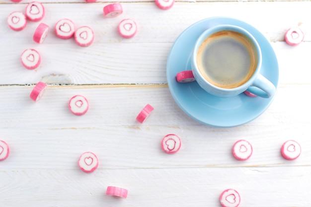 흰색 나무 테이블에 서 캔디 하트와 커피 블루 컵. 달콤한 성 발렌타인 데이