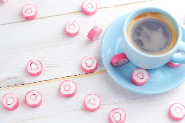白い木製のテーブルの上に立って、キャンディーハートとコーヒーの青いカップ。甘い聖バレンタインの日