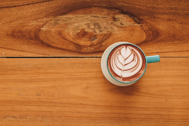 木製のテーブルにフルラテアートとコーヒーの青いカップ