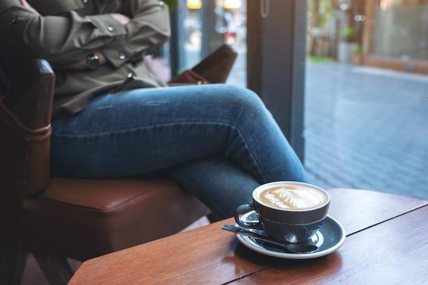 カフェに座っている女性と木製のテーブルの上のホットラテコーヒーの青いカップ