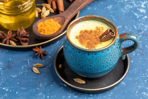 Голубая чашка традиционного индийского золотого молока латте куркумы с ручкой кардамона, аниса, меда и циннамона на сини.