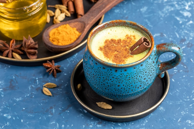 Blue cup of traditional indian golden turmeric latte milk with cardamom, anise, honey and cinnamon stick on blue.