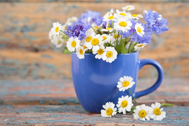 Blue cup with a bouquet of daisies and cornflowers on an old wooden background
