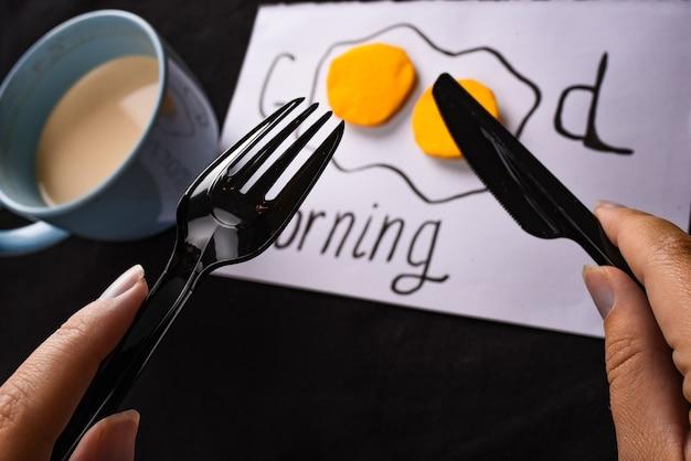 Синяя чашка с надписью кофе доброе утро яичница и руки со столовыми приборами