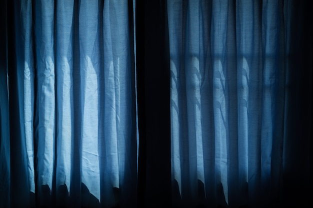 Blue curtain at window, halloween day in night on room with horror window
