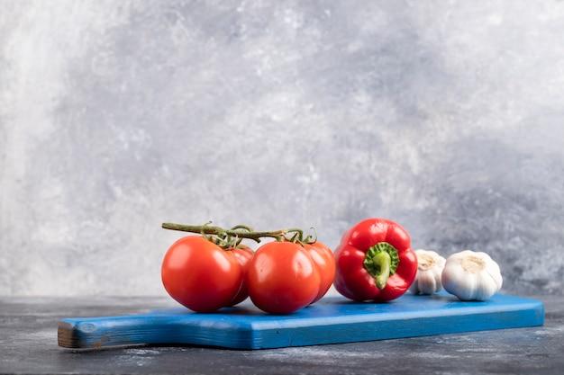 Синяя разделочная доска свежих помидоров, чеснока и перца на мраморе.