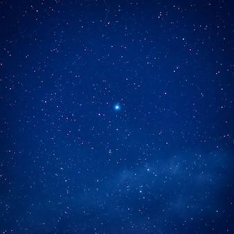Голубое темное ночное небо с большой яркой звездой в центре. космический млечный путь