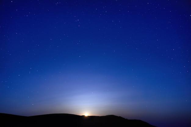 多くの星と青く暗い夜空。月が昇る。スペースの背景