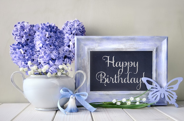 Blue decorations and hyacinth flowers on white table, blackboard with text